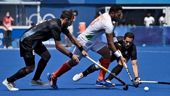 India Harmanpreet Singh is tackled by Argentina's Nahuel Salis (L) and Agustin Alejandro Mazzilli during their men's pool A match of the Tokyo 2020 Olympic Games(AFP)
