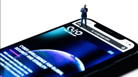 This studio photographic illustration shows a smartphone with the website of Israel's NSO Group which features Pegasus spyware, on display in Paris on July 21, 2021. (AFP)