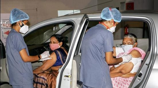 Health workers give a dose of Covid-19 vaccine to elderly women at a drive-in vaccination center in Nagpur. (PTI)