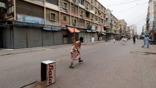 Shopkeepers play cricket along closed market during a partial lockdown after Sindh provincial government decided to shut markets.(Reuters)