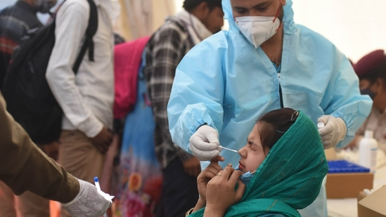 A health worker collects a swab sample for Covid-19 testing at Anand Vihar Bus Terminal, in New Delhi.(Raj K Raj/HT file photo)