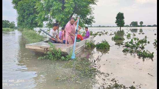 A farmer uses a boat in his submerged fields in Moonak on Friday. (HT Photo)