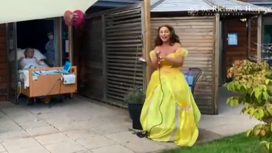 The image shows a singer singing for the 88-year-old woman on her birthday.(YouTube/@St Richard's Hospice)