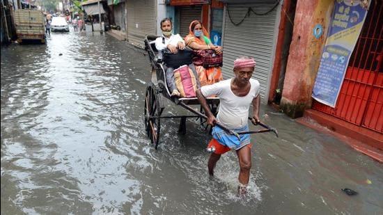A rickshaw puller carries passengers on a waterlogged road in Kolkata. (File photo)