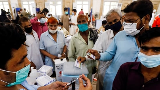 Residents with their registration cards gather at a counter to receive a dose of the coronavirus disease (Covid-19) vaccine at a vaccination center in Karachi, Pakistan June 9, 2021 (REUTERS).