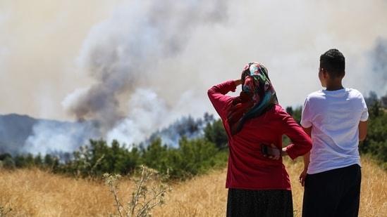 Locals watch a wildfire near the town of Manavgat, east of the resort city of Antalya, Turkey, (REUTERS/Kaan Soyturk)