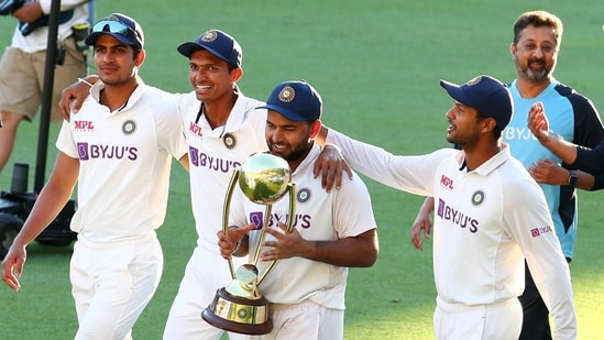 India's Rishabh Pant carries the trophy as he celebrates with his teammates after defeating Australia by three wickets on the final day of the fourth cricket test at the Gabba, Brisbane,(AP)