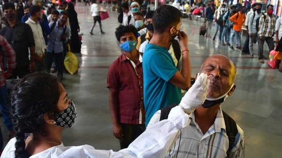 A BMC health worker collects swab samples for Covid-19 test of passengers arriving from outstation trains at CSMT station, in Mumbai. (HT PHOTO)