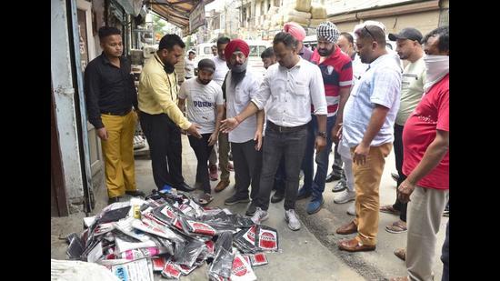 A municipal corporation team raiding shops during a drive against polythene bags in Ludhiana on Monday. (Gurpreet Singh/HT)