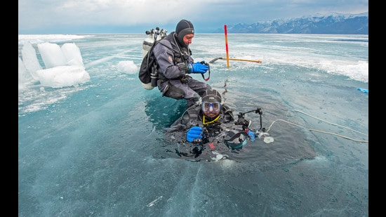 Photographer Dhritiman Mukherjee descends into an ice hole in the frozen-over Lake Baikal in Siberia. Mukherjee has been cold-water diving for five years and one of his main concerns returning to places where permanent ice structures dominate the landscape, is witnessing their depletion, he says. (Dhritiman Mukherjee)