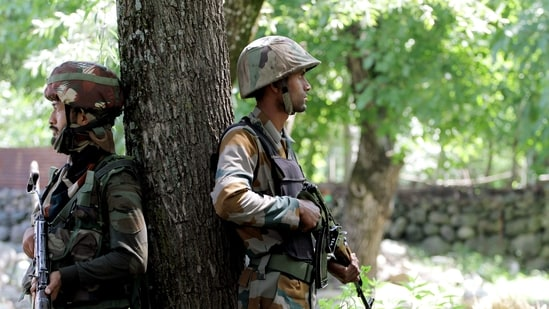 Army personnel take position during an encounter at Shokbaba forest, in Bandipora. (ANI Photo)