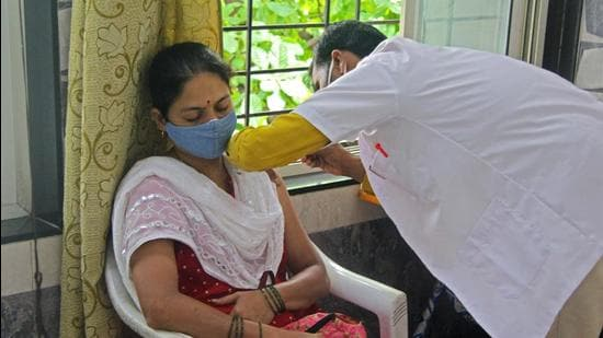A health worker vaccinates a woman at Covid 19 vaccination center in Pune. (Ravindra Joshi/HT PHOTO)