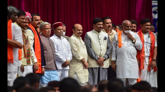 Karnataka Governor Thawar Chand Gehlot and chief minister Basavaraj Bommai with newly inducted ministers during swearing-in ceremony to form the Cabinet at Raj Bhavan in Bengaluru on Wednesday. (PTI)