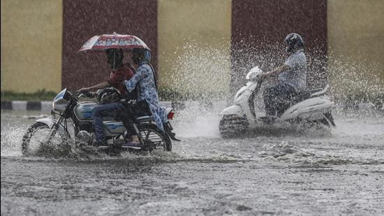Motorists wade through a waterlogged area during rainfall in Jammu. (File photo)