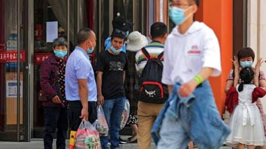 People wearing face masks to help curb the spread of the coronavirus talk to each other outside a grocery store at the Wangfujing shopping district in Beijing.(AP File Photo)