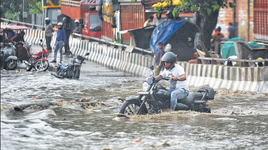 Commuters wade through a waterlogged Rohtak Road stretch near Anand Parbat on Saturday. IMD has predicted more rain on Sunday. (Sanchit Khanna/HT)
