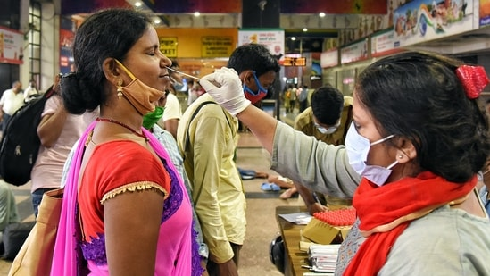 A healthcare worker collects a swab sample of a passenger for the Covid-19 test, at New Delhi Railway Station. (ANI Photo)