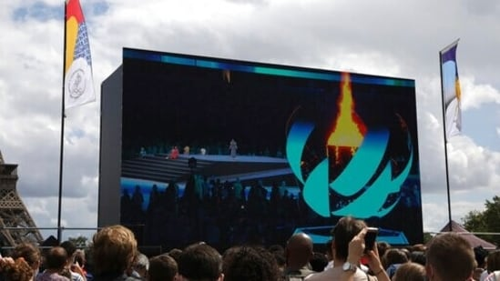 Spectators watch the closing ceremony of the Tokyo 2020 Olympic Games on a big screen at the Olympics fan zone in Trocadero Gardens in Paris, Sunday, Aug. 8, 2021. Celebrations were held in Paris Sunday as part of the handover ceremony of Tokyo 2020 to Paris 2024, as Paris will be the next Summer Games host in 2024. The passing of the hosting baton will be split between the Olympic Stadium in Tokyo and a public party and concert in Paris. (AP Photo/Adrienne Surprenant)(AP)