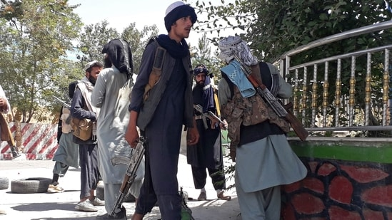Taliban fighters stand along the roadside in Ghazni as the Taliban move closer to the Afghan capital after taking Ghazni city.(AFP)