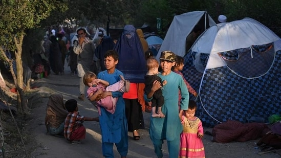 Internally-displaced Afghan families, who fled from Kunduz, Takhar and Baghlan province due to battles between Taliban and Afghan security forces, walk past their temporary tents in Kabul on August 11.(AFP Photo)