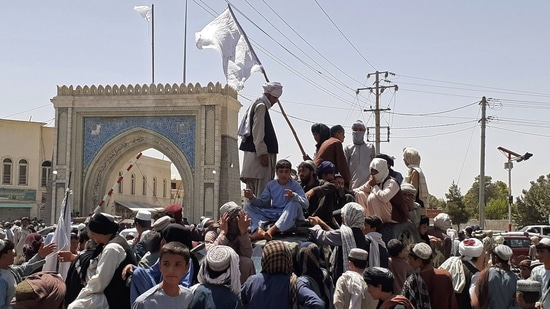 Taliban fighters stand on a vehicle along the roadside in Kandahar on August 13, 2021.(AFP)