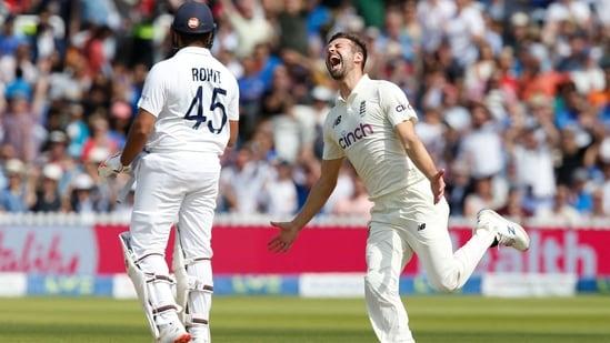 Mark Wood (R) celebrates the wicket of Rohit Sharma (L)
