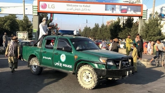 Taliban fighters on a police vehicle outside Hamid Karzai International Airport in Kabul, Afghanistan, on Monday.(Reuters Photo)