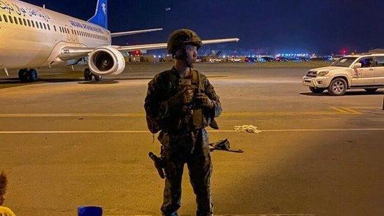 A US army soldier stands guard as Afghans wait to leave from the airport in Kabul(AFP)
