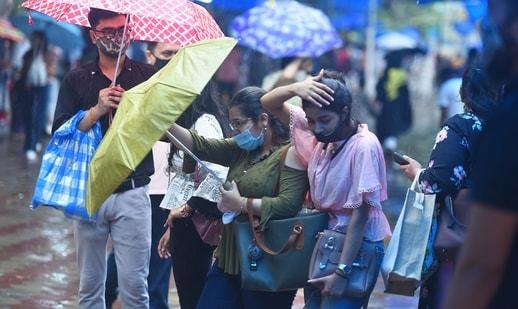 Visitors caught in the rain at Janpath market, in New Delhi last week. (Raj K Raj / Hindustan Times))