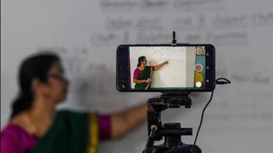 A school teacher gives a live streaming online class at a government school after the government eased a nationwide lockdown imposed as a preventive measure against the COVID-19 coronavirus, in Chennai on June 3, 2020. (Photo by Arun SANKAR / AFP) (AFP)