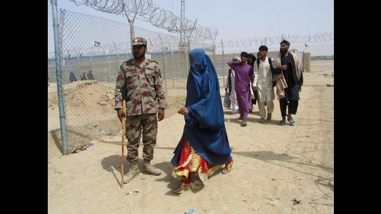 An Afghan woman walking past a Pakistani paramilitary personnel, as she along with others enter Pakistan via Friendship Gate crossing point at the Pakistan-Afghanistan border town of Chaman on Tuesday. (Reuters)