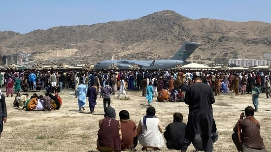 Hundreds of people gather near a US Air Force C-17 transport plane at a perimeter at the international airport in Kabul, Afghanistan, Monday, Aug. 16, 2021.(AP)
