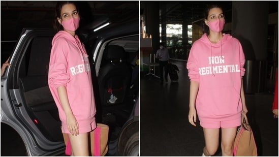 Kriti teamed her attire with a pink face mask, white lace-up sneakers and a brown large tote bag. She tied her locks in a middle-parted hairdo and chose dewy skin to style the look.(Varinder Chawla)