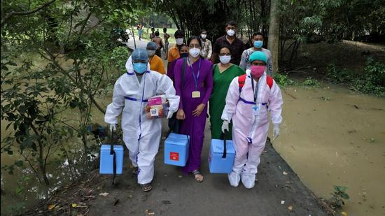Healthcare workers carry vaccines during a door-to-door vaccination and testing drive in West Bengal. (REUTERS File)
