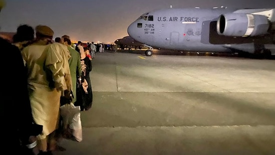 Afghans queue up and board a US military aircraft in Kabul after the Taliban's takeover of Afghanistan. (AFP Photo)