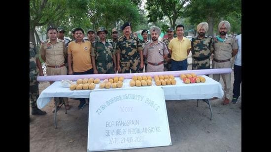 The joint team of the BSF and Amritsar (rural) police with the drugs seized near the Panjgrain border outpost along the Pakistan border in Dera Baba Nanak sector on Saturday. (HT Photo)