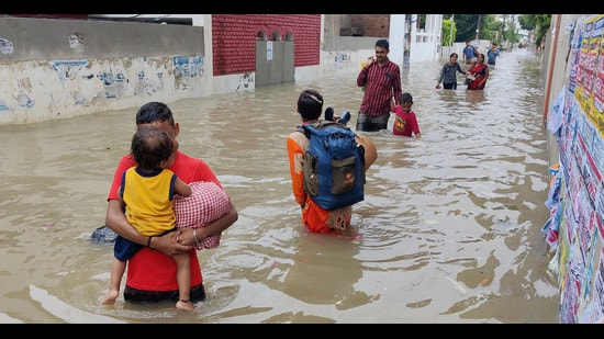 People wade through a flooded road after heavy downpour in Bathinda, Sunday (PTI)