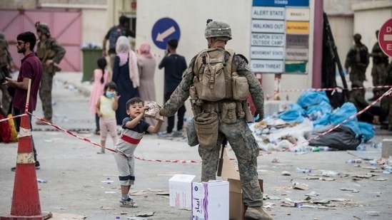 A US Marine provides a meal ready-to-eat to a child during an evacuation at Hamid Karzai International Airport, Kabul, Afghanistan,(via REUTERS)