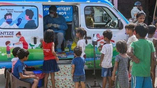 Underprivileged children wait outside a van decorated with toys for their Covid-19 test in New Delhi. (ANI PHOTO.)