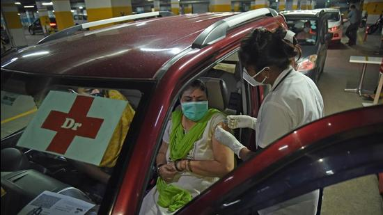 A beneficiary gets inoculated against Covid-19 at a drive-in vaccination centre at Inorbit Mall basement parking, Vashi, in Navi Mumbai on Monday. (Bachchan Kumar/ HT PHOTO)