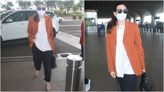 Karisma carried a black top handle bag with her boss lady attire. She completed her airport look with grey suede shoes, sunglasses, a chunky gold chain, and a face mask. She tied her locks in a sleek ponytail and kept her make-up minimal.(HT Photo/Varinder Chawla)