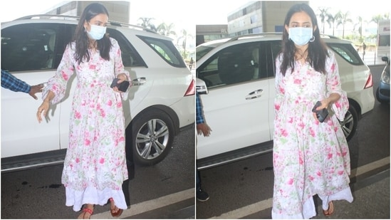 Rakul's airport look featured a white anarkali adorned with pink and green floral print. The kurta had a billowy silhouette with a cinched-in detail at the waist and bell sleeves.(HT Photo/Varinder Chawla)