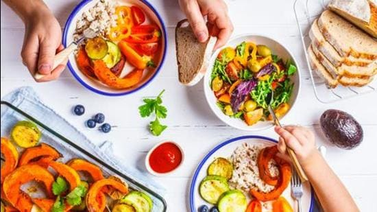 Flat lay of family hands eating healthy food. Vegan lunch table top view. Baked vegetables, fresh salad, berries, bread on a white background. (Getty Images/iStockphoto)