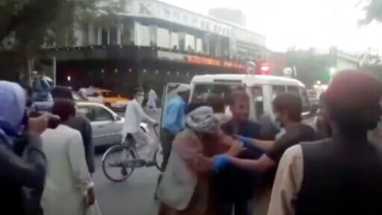 In this image taken from video, people tend to a wounded person near the site of a deadly explosion outside the airport in Kabul, Afghanistan,(AP)