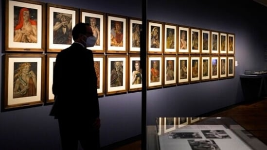 A women takes a photo of the artwork 'Demons of the Hour' by artist Werner Peiner at the exhibition 'Divinely Gifted List' at the German Historic Museum in Berlin, Germany. The exhibition at the German Historical Museum traces the lives and creations of several artists who made it onto the so-called 'Divinely Gifted List' from 1944, which was compiled on behalf of Adolf Hitler and other top Nazis.(AP Photo/Markus Schreiber)