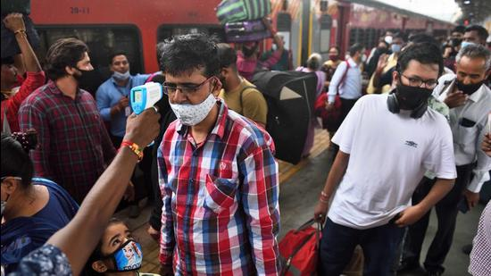 A BMC health worker checks temperatures before Covid-19 test of commuters arriving on outstation trains at Dadar station, in Mumbai on Thursday, August 26. (Satish Bate/HT photo)