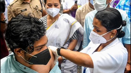 Thiruvananthapuram: A medic administers a dose of Covid-19 vaccine to a beneficiary in the presence of Kerala Minister for Health Veena George, during State's first drive-through vaccination, at Government Womens college in Thiruvananthapuram, Thursday, August 19, 2021. (PTI Photo)(PTI08_19_2021_000048B) (PTI)