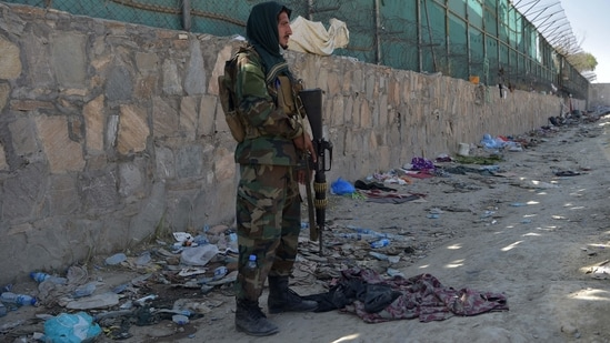A Taliban fighter stands guard at the site of the attacks, in Kabul airport on Friday.(AFP)