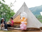 A young couple with their dog spend their time outside an Indiana-style tent at We Camp, a glamping site located in Yuen Long, Hong Kong The difficulty of travelling abroad has made glamping, or glamourous camping, popular in Hong Kong.(AP Photo/Matthew Cheng)