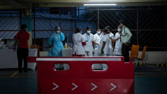Health workers converse during a drive-in facility for Covid-19 vaccination at a car parking area of a shopping mall in Kochi, Kerala, on Friday, Aug.27, 2021. (AP)